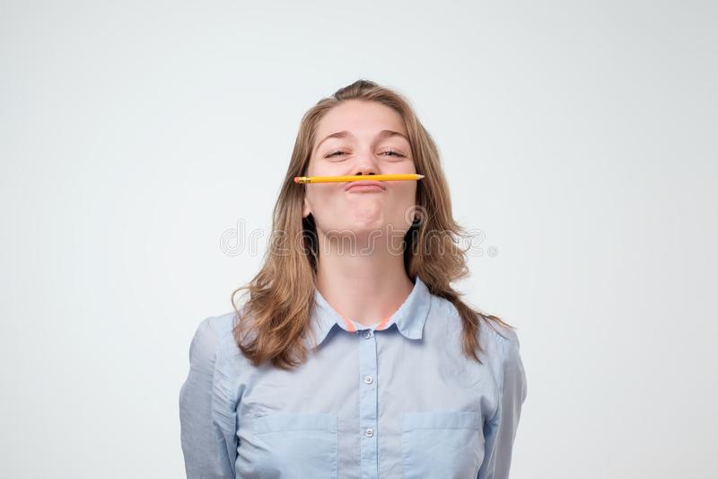Young beautiful student holding pen between nose and lips as mustache looking funny and naughty stock photos