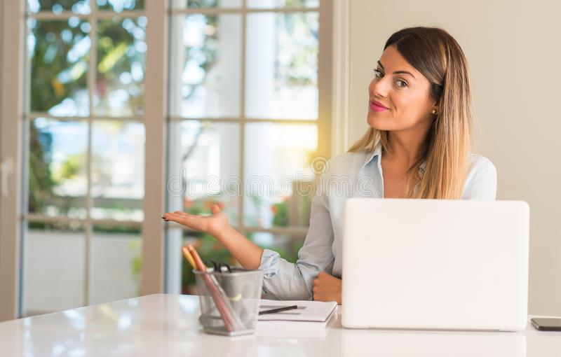 Young beautiful student woman with laptop at table, at home. Student woman at table with laptop at home confident and happy with a big natural smile inviting to royalty free stock photography