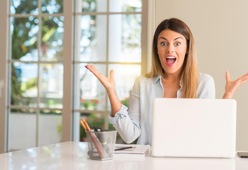 Young beautiful student woman with laptop at table, at home. Student woman at table with laptop at home happy and surprised cheering expressing wow gesture royalty free stock photography