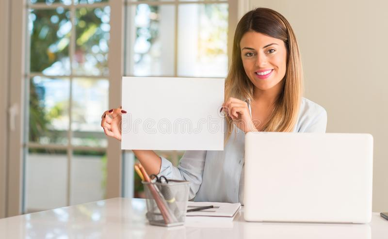 Young beautiful student woman with laptop at table, at home. Student woman at table with laptop at home holding blank advertising banner, good poster for ad stock photo