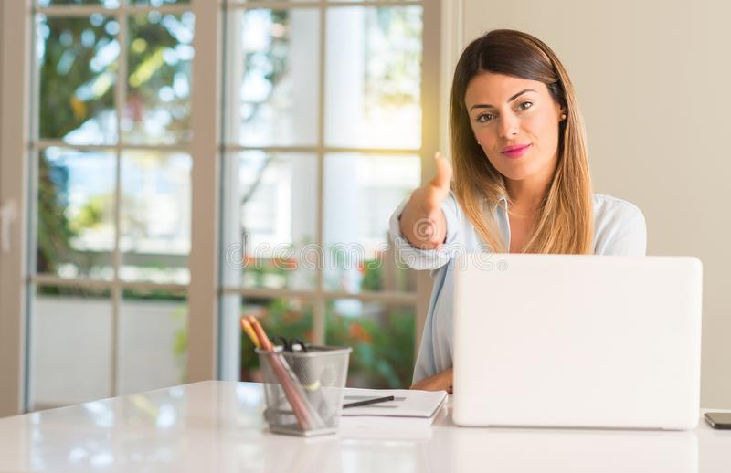 Young beautiful student woman with laptop at table, at home. Student woman at table with laptop at home holds hands welcoming in handshake pose, expressing trust stock photography