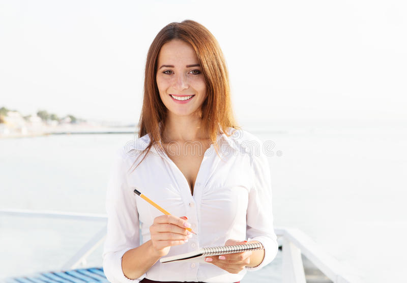 Young beautiful student writes in a notebook on thesea backgrou. Young beautiful student writes in a notebook on the background of the sea stock photos