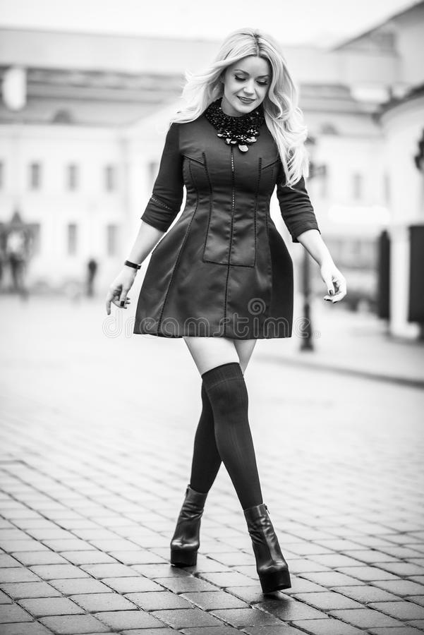 Young beautiful stylish classy girl wearing black dress. Standing and posing in the city stock photo