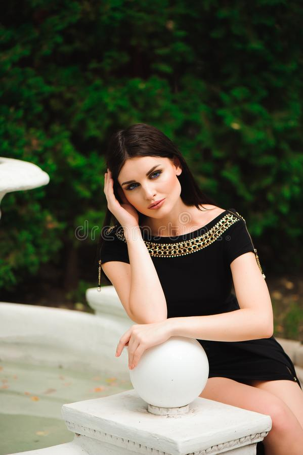Young beautiful stylish girl walking and posing in short black dress in city near fountains. Outdoor summer portrait of royalty free stock photo