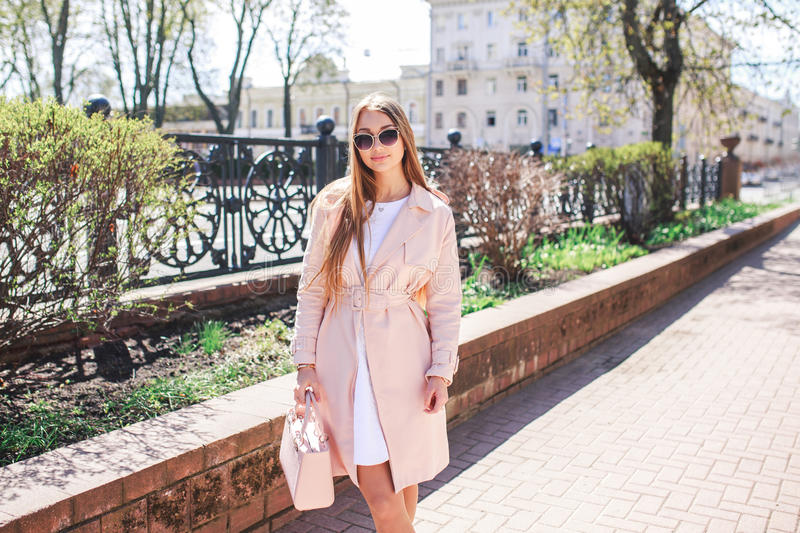 Young beautiful stylish girl walking and posing in white dress and pink coat in city . Outdoor summer portrait of young classy wom stock photos