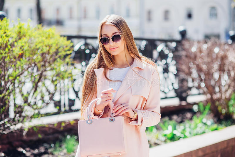 Young beautiful stylish girl walking and posing in white dress and pink coat in city . Outdoor summer portrait of young classy wom royalty free stock images