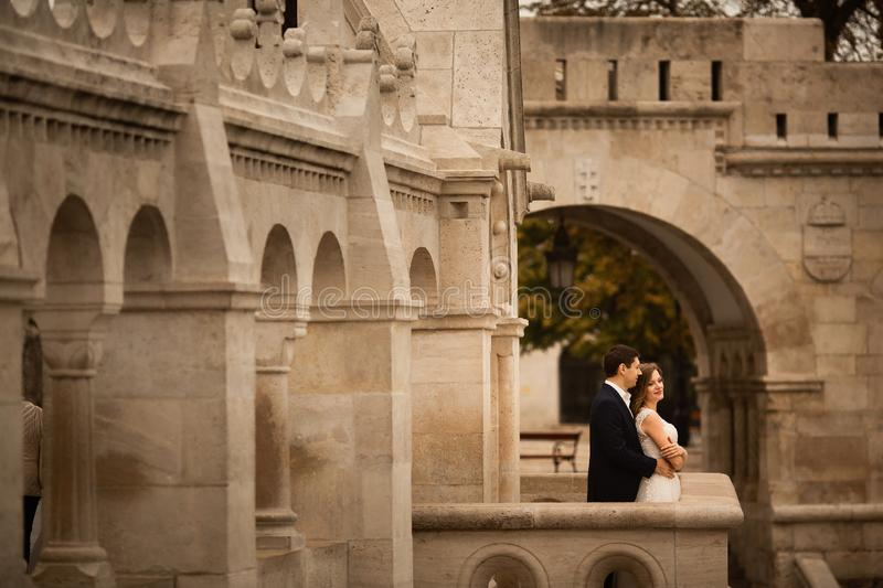 Young beautiful stylish pair of newlyweds hugging by the Fisherman`s Bastion in Budapest, Hungary royalty free stock photography