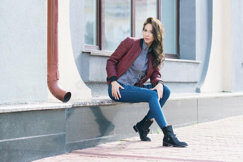 Young beautiful stylish woman in a burgundy pilot`s jacket and blue jeans, street style, spring and autumn trend, look, hair in t. He wind royalty free stock photography