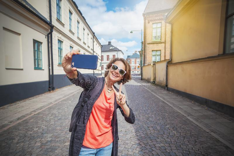 Young beautiful stylish woman with mobile phone in hands on city royalty free stock images