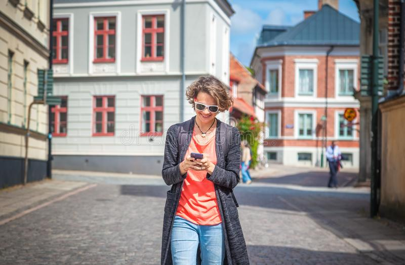 Young beautiful stylish woman with mobile phone in hands on city royalty free stock photography