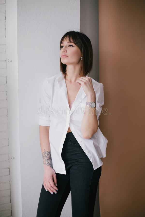 Young beautiful stylish woman with a tattoo in a studio royalty free stock image