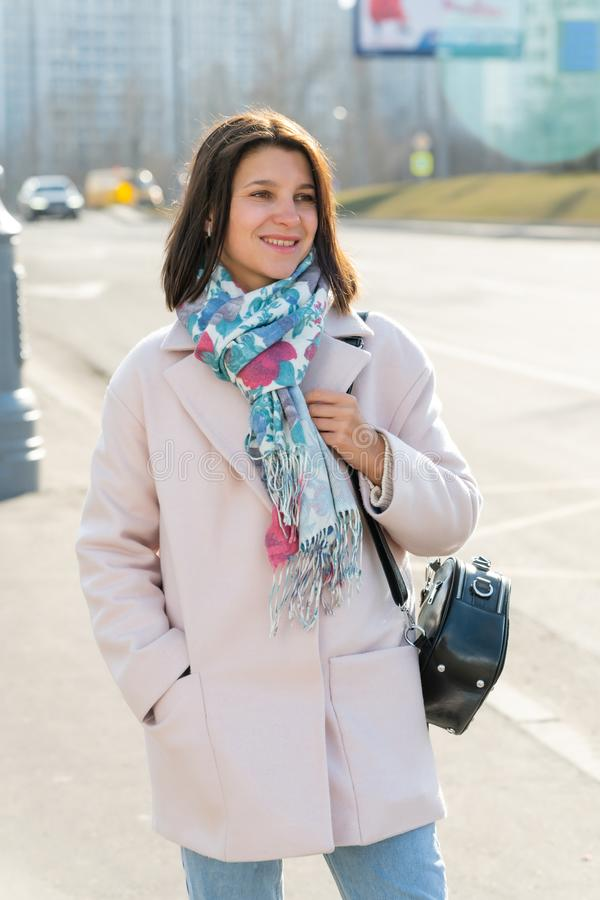 young beautiful stylish woman walking down the street in pink coat, autumn fashion trend, smiling, happy stock photography