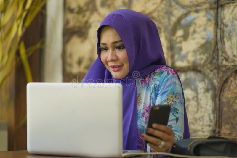 Young beautiful and successful Asian woman in traditional hijab head scarf working on laptop computer and mobile phone running royalty free stock images