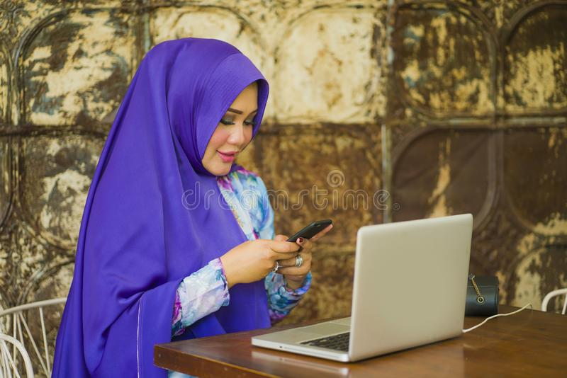 Young beautiful and successful Asian woman in traditional hijab head scarf working on laptop computer and mobile phone running stock photography