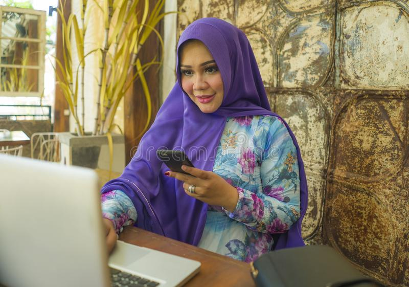 Young beautiful and successful Asian woman in traditional hijab head scarf working on laptop computer and mobile phone running stock image