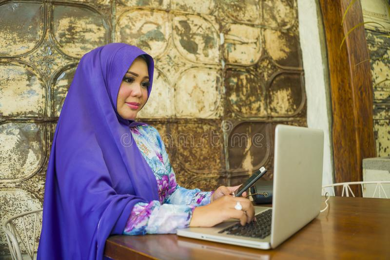 Young beautiful and successful Asian woman in traditional hijab head scarf working on laptop computer and mobile phone running stock photos