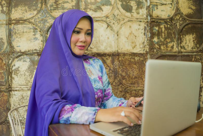 Young beautiful and successful Asian woman in traditional hijab head scarf working on laptop computer and mobile phone running royalty free stock photos
