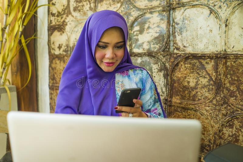 Young beautiful and successful Asian woman in traditional hijab head scarf working on laptop computer and mobile phone running royalty free stock photography
