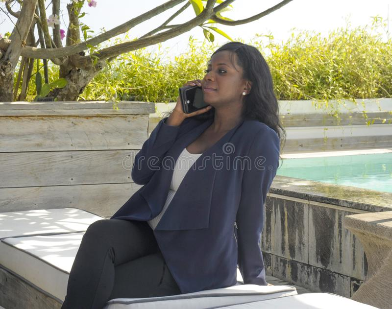 Young beautiful and successful black Afro American woman on her 30s wearing formal business clothes sitting at pool resort working stock photography