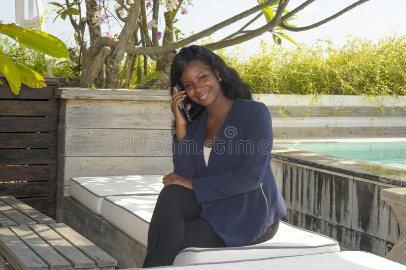 Young beautiful and successful black Afro American woman on her 30s wearing formal business clothes sitting at pool resort working royalty free stock photo