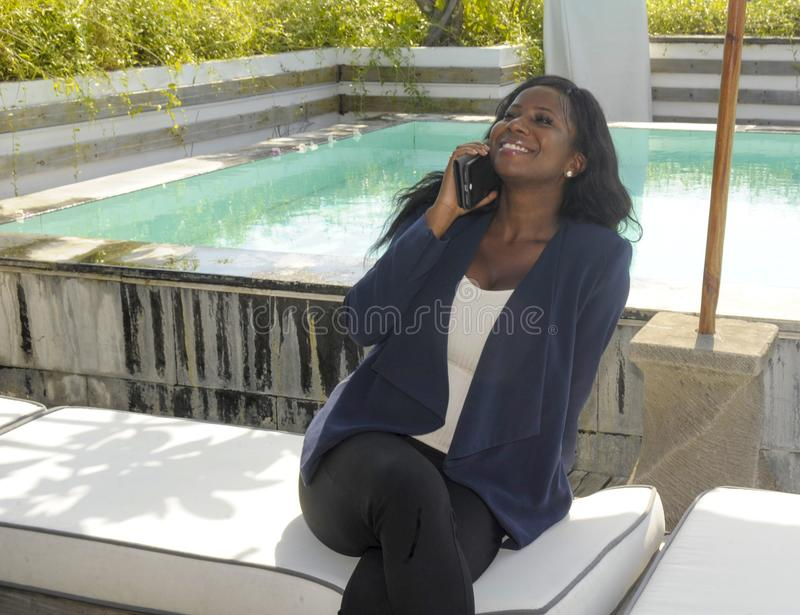 Young beautiful and successful black Afro American woman on her 30s wearing formal business clothes sitting at pool resort working stock photos