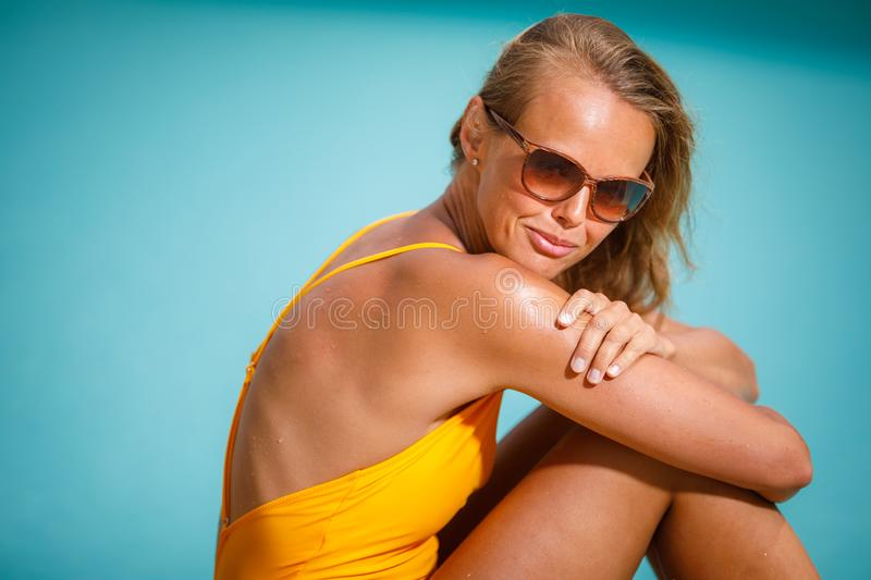 Young Beautiful Suntanned Woman wearing sunglasses. Relaxing next to a Swimming Pool on a lovely Summer Day stock images