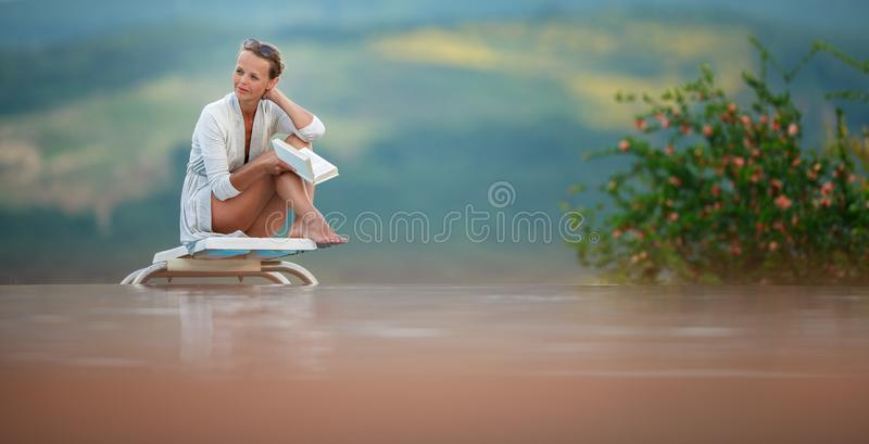 Young Beautiful Suntanned Woman relaxing next to a Swimming Pool. Young Beautiful Suntanned Woman wearing sunglasses relaxing next to a Swimming Pool on a lovely stock image