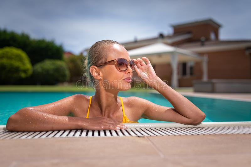 Young Beautiful Suntanned Woman wearing sunglasses relaxing next to a Swimming Pool. On a lovely Summer Day royalty free stock photo