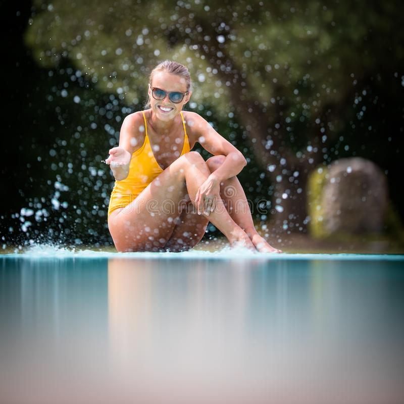 Young Beautiful Suntanned Woman wearing sunglasses. Relaxing next to a Swimming Pool on a lovely Summer Day stock image