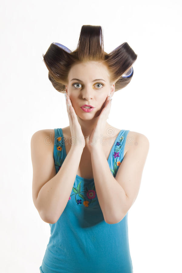 Young beautiful surprised woman in hair curlers royalty free stock photography