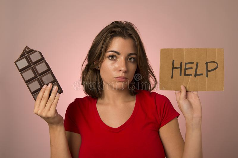 young beautiful sweet addict woman holding asking for help resisting temptation to eat chocolate bar and break diet stock image