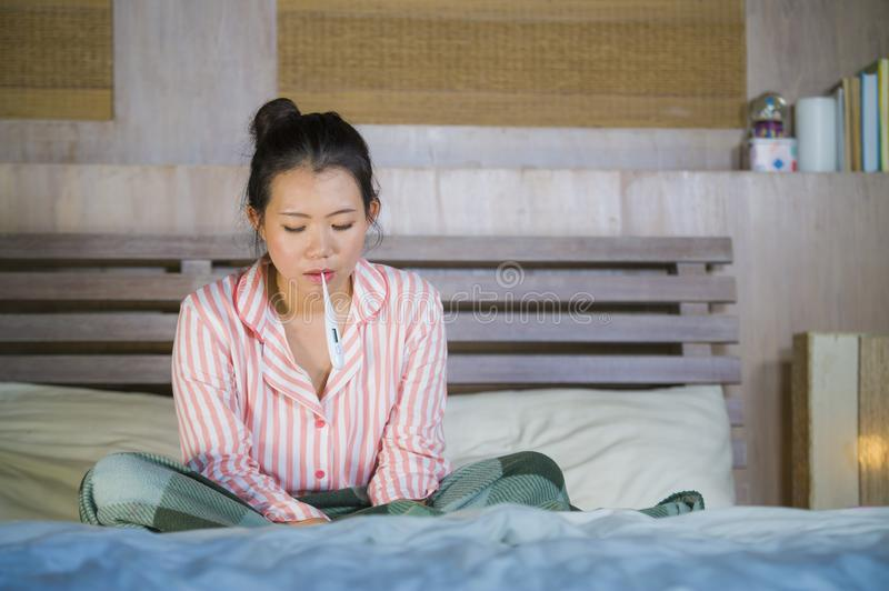 Sweet Asian Korean girl in pajamas covered with blanket sick suffering cold and flu taking temperature with thermometer in bed royalty free stock photos