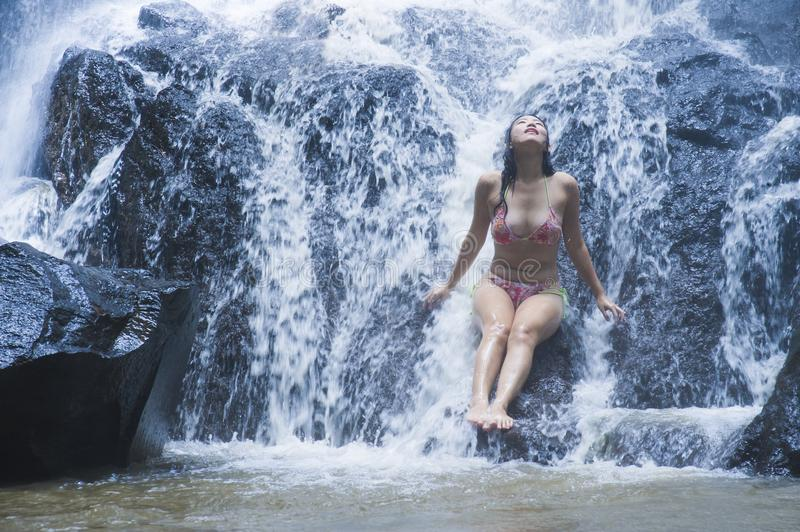 Young beautiful and sweet Asian woman in bikini getting body wet under stream of natural amazing waterfall sitting on rock feeling stock image