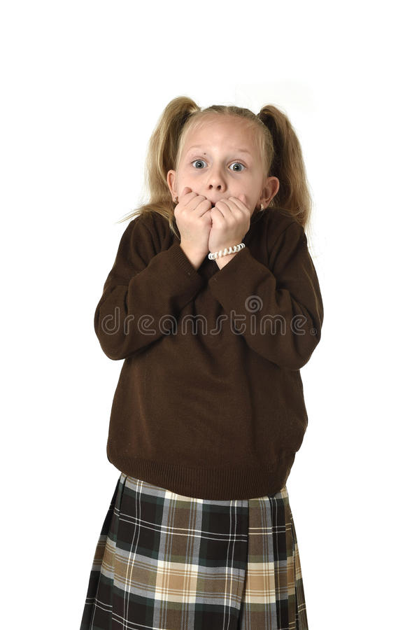 Young beautiful and sweet schoolgirl in pigtails and school uniform looking amazed and scared. Young beautiful and sweet schoolgirl in pigtails and school stock photo
