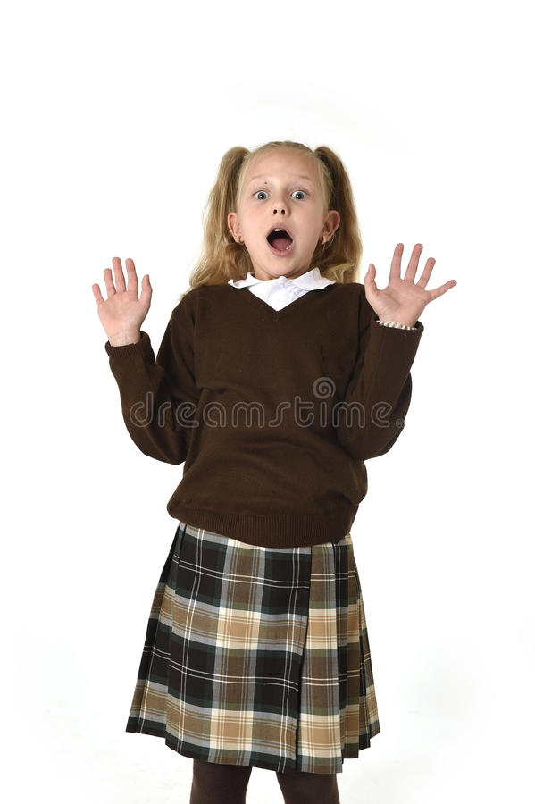 Young beautiful and sweet schoolgirl in pigtails and school uniform looking amazed and scared. Young beautiful and sweet schoolgirl in pigtails and school stock images