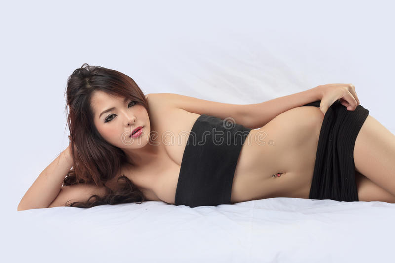 Young beautiful tanned Asian woman posing on bed royalty free stock photography