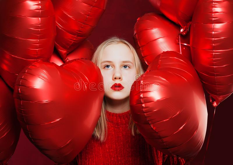 Young beautiful teen girl looking up on red heart balloons background royalty free stock photo