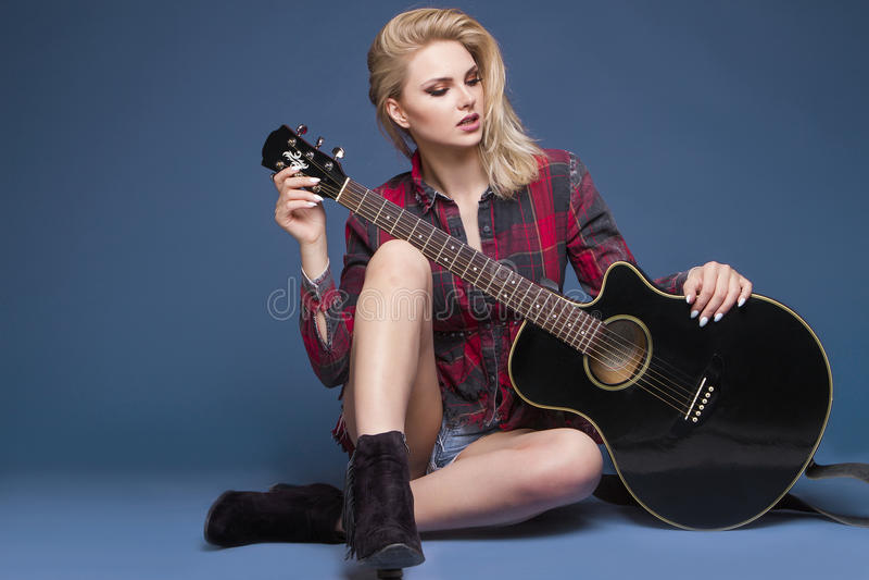 Young beautiful teenage girl playing on guitar. Concert. Hobby. stock photo
