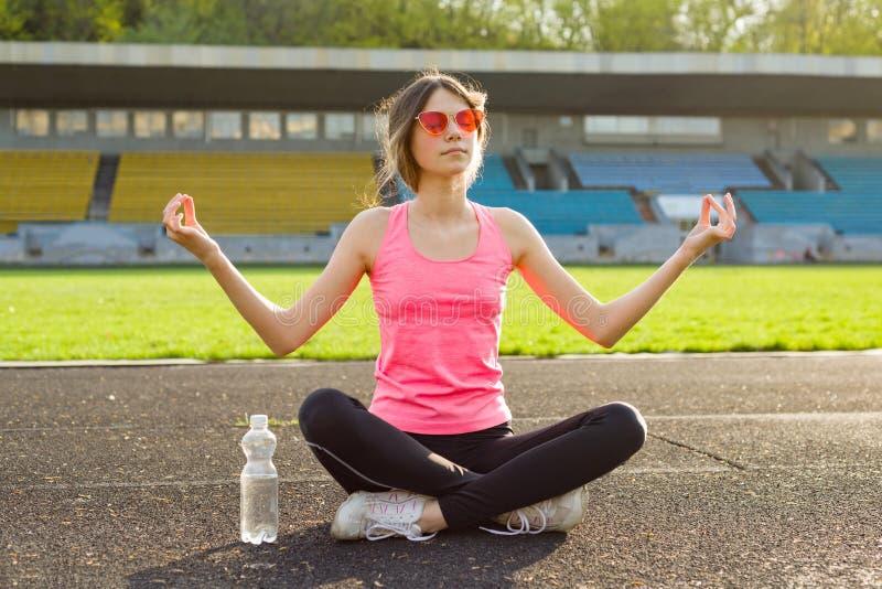 Young beautiful teenage girl practicing yoga in the stadium stock photography