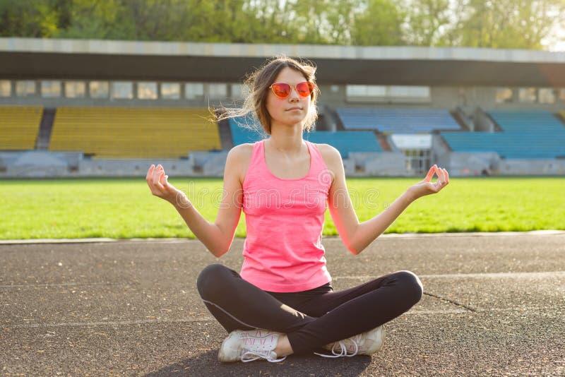 Young beautiful teenage girl practicing yoga in the stadium. stock photos