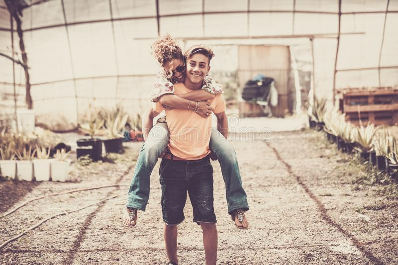 Young beautiful teenager play with his mother middle age pretty woman carrying her to his back. couple mother son having fun stock images