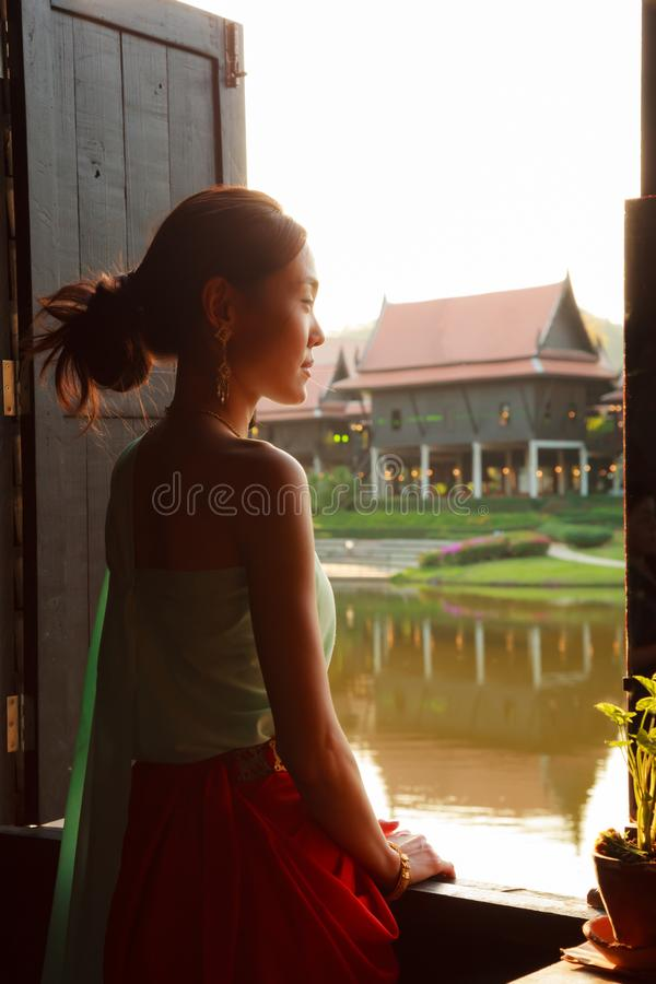 Young Beautiful Thai Asian woman dressing in vintage retro Traditional Thai costume looking out of window. Thailand Cultural and stock image