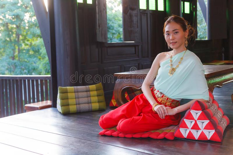 Young Beautiful Thai Asian woman dressing vintage Traditional Thai costume sits on triangle cushion at balcony. Thailand Cultural stock photo