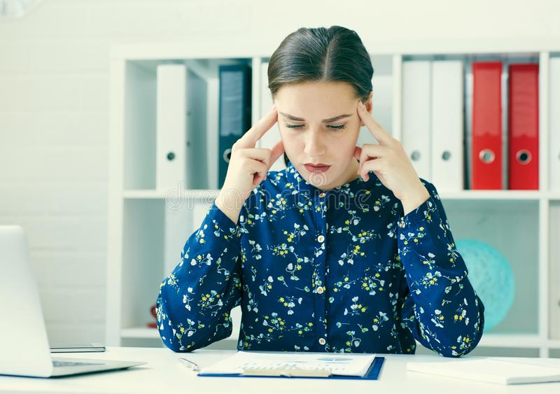 Young beautiful thoughtful business woman sitting at office workplace looking at the graphs. royalty free stock photo