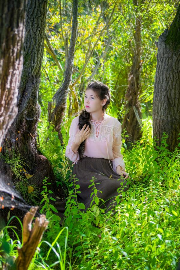 Girl sits under a tree in the forest. royalty free stock image