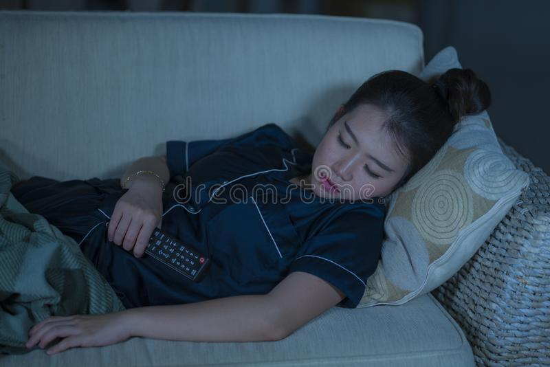 Young beautiful and tired Asian Korean woman in pajamas holding TV remote falling asleep on living room sofa couch while watching stock photos