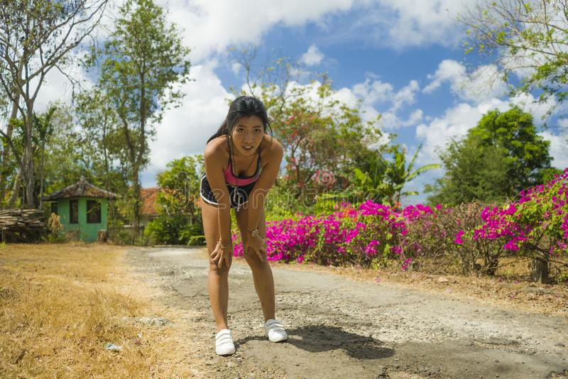Young beautiful tired and breathless runner Asian woman exhausted and sweaty after hard running workout at trail road park in royalty free stock photo