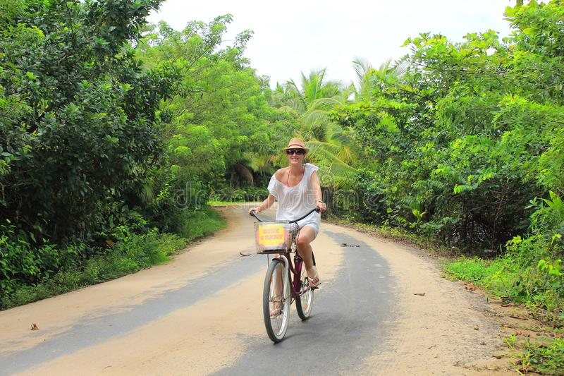 Young beautiful tourist riding a bike in the sand roads of Bocas del Toro islands in Panamá stock photography