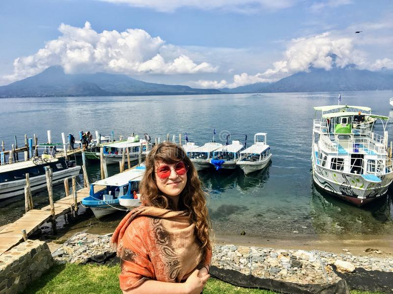 A young beautiful tourist standing at the shores of Lake Atitlan, with the beautiful calm water and volcanoes in the background. stock image