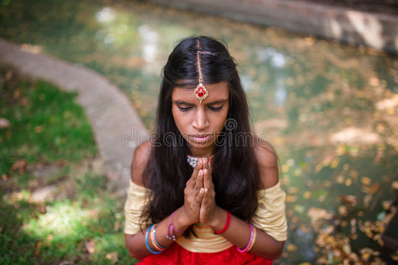 Young beautiful traditional indian woman praying outdoors. In nature stock photography